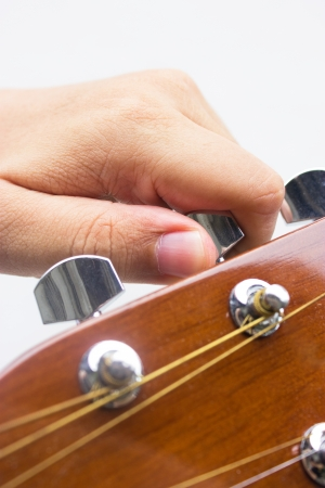 guitar tuner: Hand tuning a guitar from headstock isolated on white background  Stock Photo