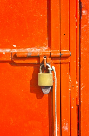 withhold: Red metal door locked by key.