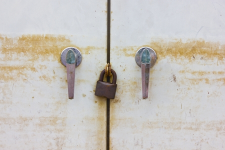 restrictive: Dirty cabinet locked by old and rusty key. Stock Photo
