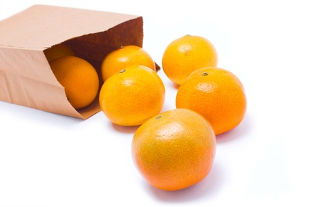 trundle: Six oranges falling from paper bag, isolated on white background