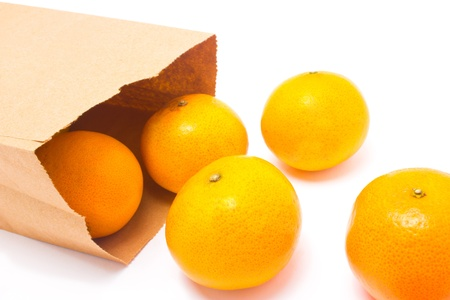 trundle: Oranges falling from paper bag, isolated on white background