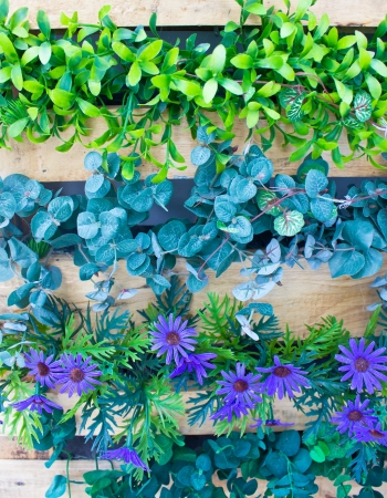 vertical image: Plaastic flowers and plants in wooden pot as vertical garden