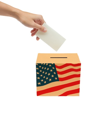 Hand putting a voting ballot into the box isolated on white background  photo