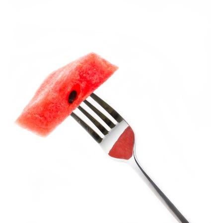 Piece of watermelon with fork isolated on white background. photo