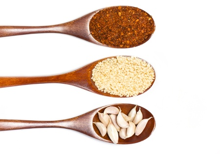 Sesame seeds on wooden spoon isolated on white background. photo