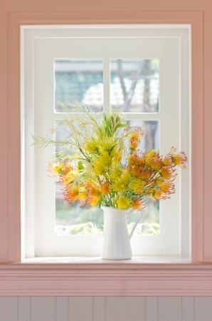 Artificial flowers in white vase beside white window. photo