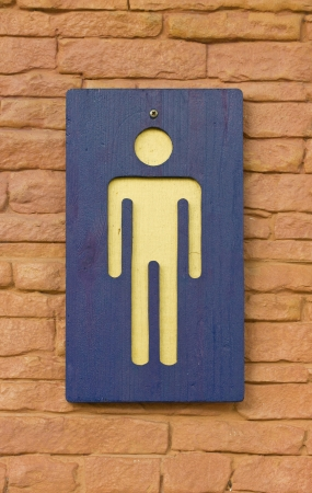 Male toilet sign on the brick wall. photo