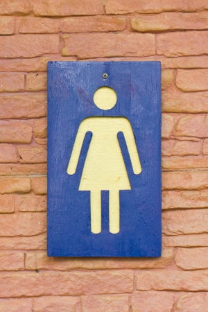 female toilet sign on the brick wall. photo