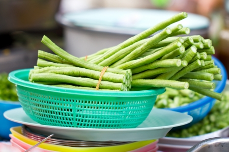 Pieces of yardlong bean in green plastic basket  photo