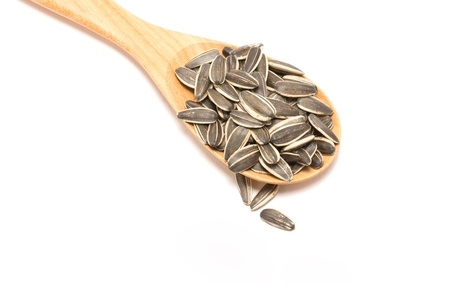 Sunflower seeds with wooden spoon isolated on white background. photo