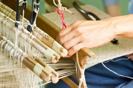 machine made: Close up of silk weaved machine with hand. Stock Photo