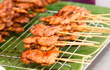 person appetizer: Thai style BBQ pork on metal sieve. Stock Photo
