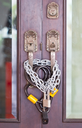 Part of wooden door with chain and lock  photo