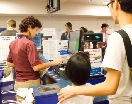 BANGKOK - MARCH 6, 2013: Visitors  in a queue at cashier counter with volunteer on board of The Logos Hope The 132.5m long ship host the world