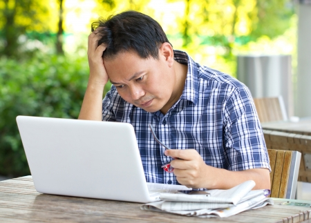 exhausted: Stress Asian man looking at laptop  Stock Photo