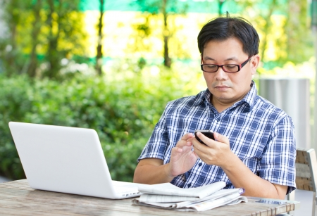 Asian man touching smart phone with white laptop