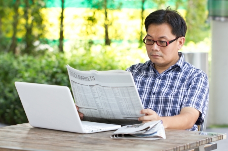Asian man reading the financial newspaper with white laptop
