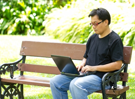 Asian man working with laptop in the park. photo