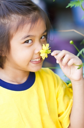 Little girl smelling A Yellow Cosmos Flower. photo