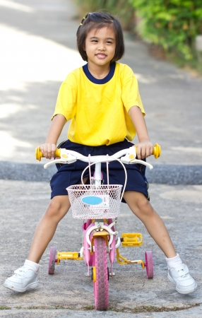 Little Asian Girl With Her Bicycle. photo