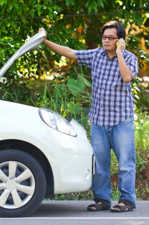 broke: Asian man standing in front of a broken car and talking with the phone. Stock Photo