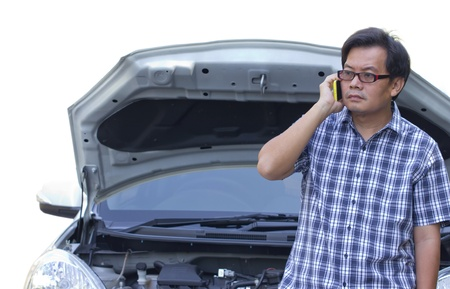 Asian man standing in front of a broken car and talking with the phone. Stock Photo