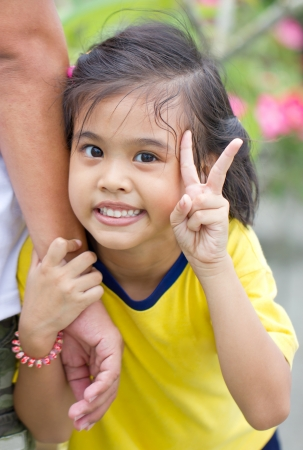 Happy Little Asian Girl Showing Victory Sign. photo