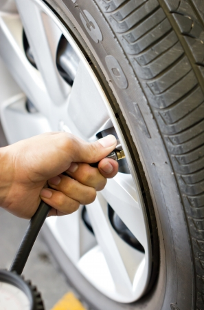 Man's hand checking tyre pressure  photo