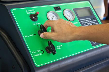 男の手が窒素タイヤ充填システム機での作業します。
