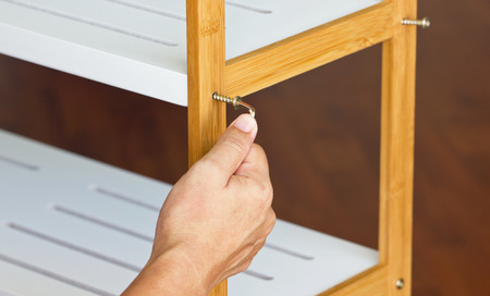 chipboard: Asian mans hand screw up wooden shelf with hex wrench