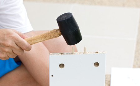furniture hardware: Furniture Assembling With Rubber Hammer. Stock Photo