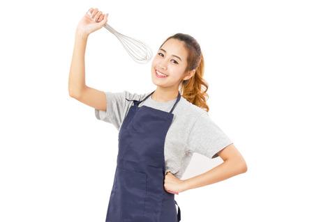 mandil: Mujer asiática que desgasta el delantal y cantando con un batidor aislado en blanco. Foto de archivo