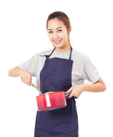 Asian Woman Wearing Apron And Showing Pot With Utensil Stockfoto
