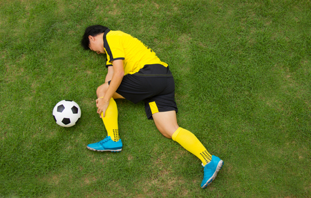 jugador de futbol: Football player in Yellow lying injured on the pitch.