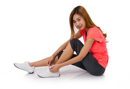 mujeres fitness: Asian young woman tying running shoes laces Isolated on white. Foto de archivo