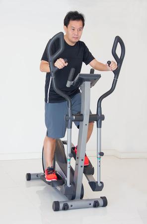 eliptica: Asain hombre hace ejercicios en la el�ptica de Al gimnasio.