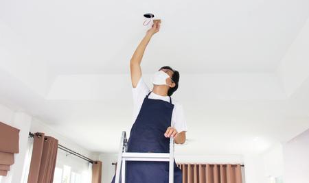 집에서 빛을 고정하는 남자. 스톡 콘텐츠