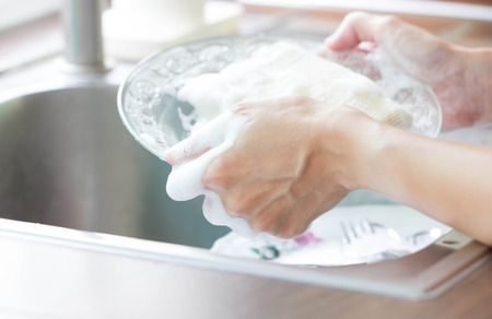 Close Up Woman Hand Holding Yellow Sponge And Washing Saucer With Washed Dishes 写真素材