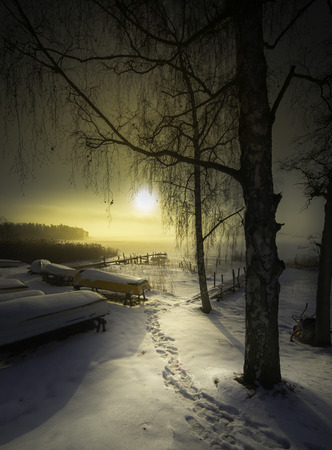 Someone went fishing in the misty morning and sun in the cold winter of Sweden