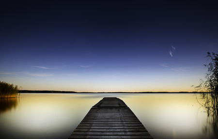 A vibrant sky and waters down by the lake and wooden pier Фото со стока