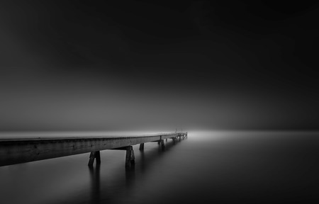Dense fog in the morning by the long wooden pier in the ocean