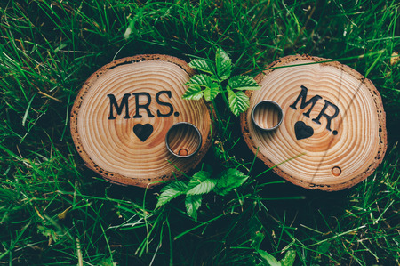 mr and mrs: Two wedding rings laying on wood boxes on grass