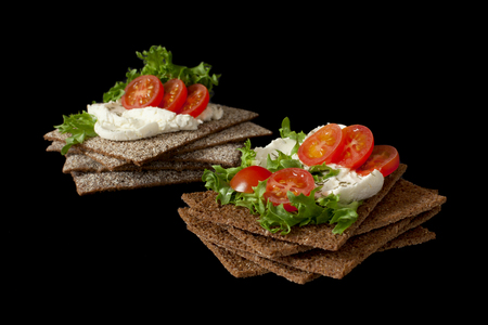 Healthy snack from wholegrain rye crispbread cracker with Cherry tomatoes, salad and soft cheese on black background