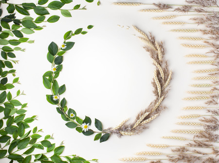Creative layout of changing seasons from summer to autumn. Wreath of green leaves and wheat. Flat lay with copy space.
