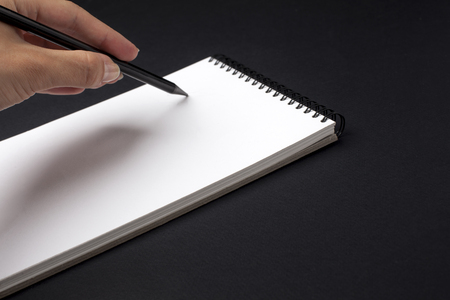 Human hand with pencil prepare to writing on notebook. Black background.