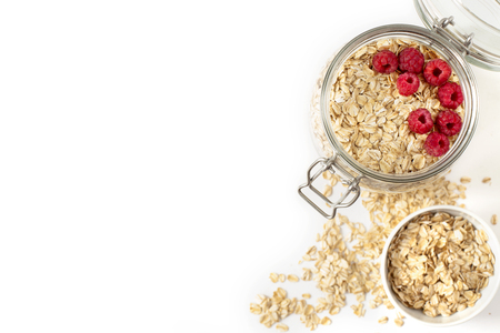 Breakfast of oatmeal with berries in a jar on white background