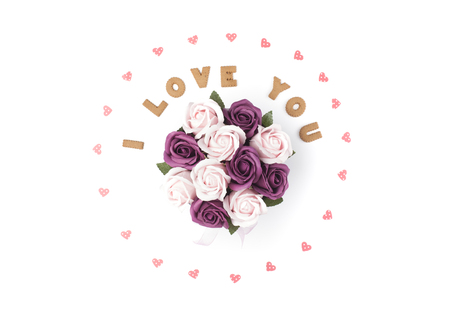 Valentines day concept. Declaration of love, frame made of paper hearts. In the center flowers in a box. Flat lay, top view, white background, isolated, copy space