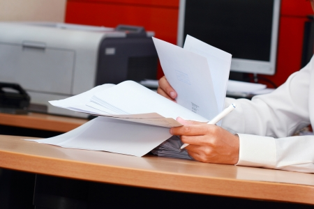 a worker man analyzing pile of paper photo