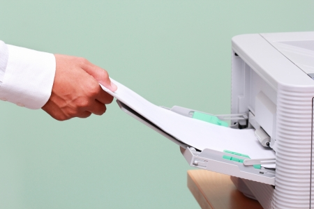 faxing: Businessman working with printer in the office