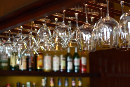 Empty glasses for wine above a bar rack Stock Photo
